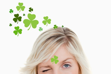 Blonde woman winking on shamrock background for st patricks day Stock Photo