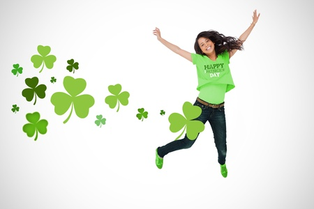 Girl wearing patricks day tshirt jumping for joy on white shamrock background photo