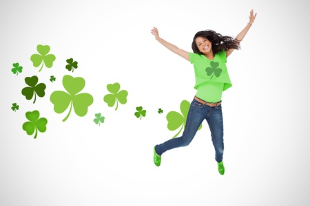 saint patty: Ragazza che porta verde trifoglio tshirt salti di gioia su trifoglio sfondo