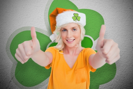 Girl in orange t-shirt giving thumbs up on wall style shamrock background Stock Photo - 18133350