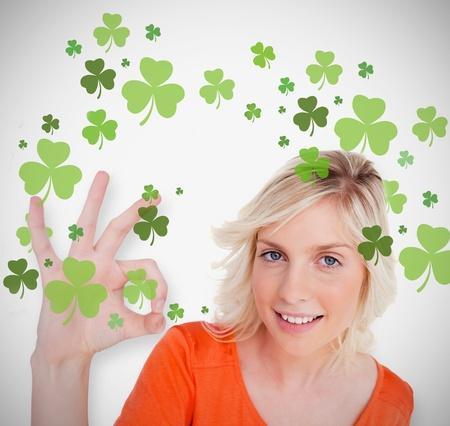 ok symbol: Blonde dando ok simbolo per St Patricks Day e sorridente su sfondo trifoglio