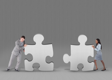 Business people pushing two jigsaw pieces together on grey background photo