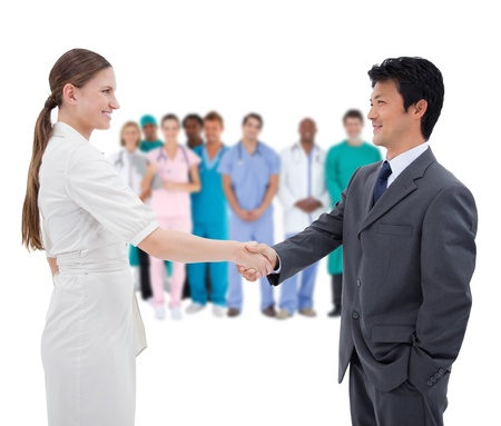 Business people shaking hands with medical staff in background on white background