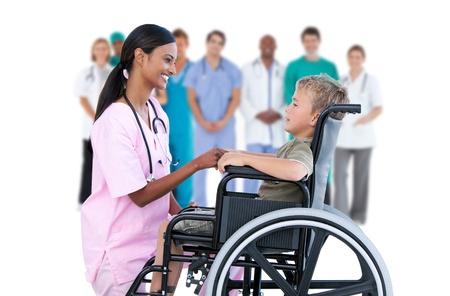 staff medico: Infermiera chiacchierando con ragazzino in sedia a rotelle con il personale medico in background