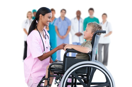 Nurse chatting with little boy in wheelchair with medical staff in background photo