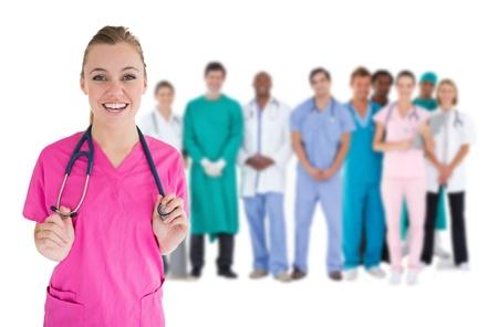 staff medico: Sorridente infermiera con il personale medico dietro di lei su sfondo bianco Archivio Fotografico