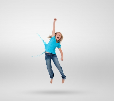 Little girl jumping with clothes turning to paint splashes on grey background photo