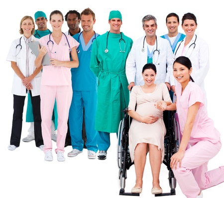 Nurse with pregnant woman in wheelchair with medical staff standing behind on white background photo