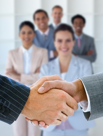 dandose la mano: Los hombres de negocios d�ndose la mano con la sonrisa del equipo de negocios detr�s de ellos