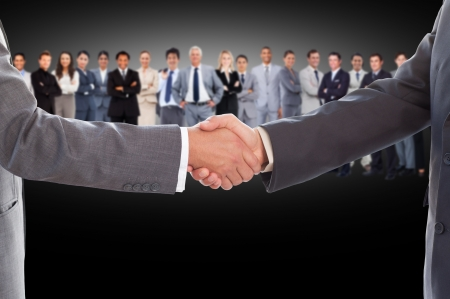 Businessmen shaking hands with large business team behind them on black backgroun photo