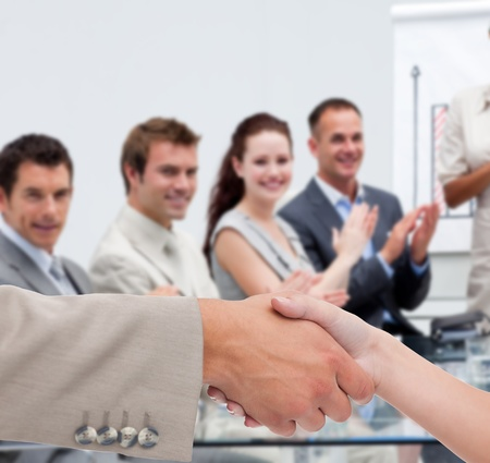 Businessman and woman shaking hands in presentation with business team clapping Stock Photo