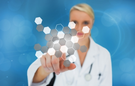 Doctor pressing touchscreen displaying hologram on blue background Stock Photo - 18132193