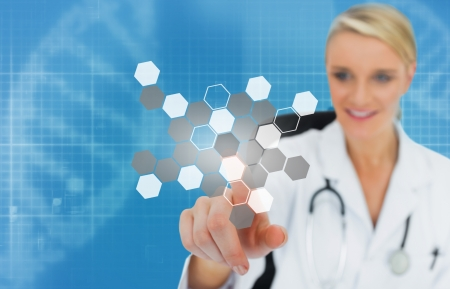 Blonde doctor using touchscreen displaying chemical formula on blue background Stock Photo - 18132266