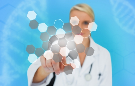 Blonde doctor pressing touchscreen displaying chemical formula on blue background Stock Photo - 18132031