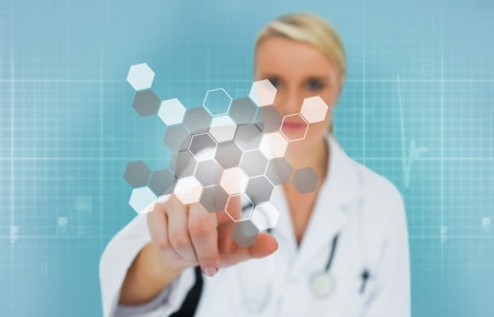 Blonde doctor using touchscreen displaying chemical formula on blue background Stock Photo - 18132177