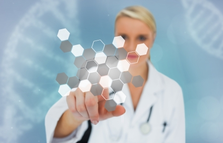 Blonde doctor selecting touchscreen displaying chemical formula on a blue background with dna Stock Photo - 18132129