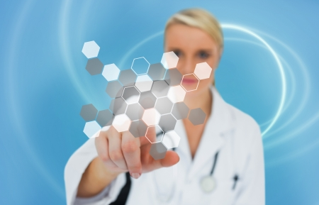 Doctor touching touchscreen displaying hologram on a blue background Stock Photo - 18132146