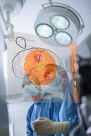 Two surgeons looking at the brain on an interface in surgery photo