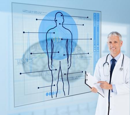 signos vitales: Mayor del doctor sonriente que sostiene un sujetapapeles junto a pantallas de visualizaci�n