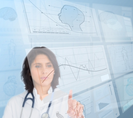 Serious woman doctor using futuristic interfaces photo
