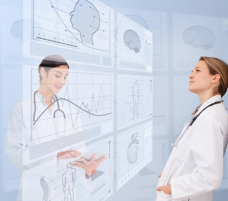 Calm women doctors using futuristic interfaces  photo