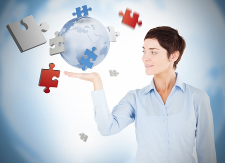 Cheerful woman with puzzles and a globe levitating Stock Photo - 18131848