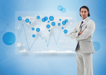Businessman standing against a digital world map and graphs photo