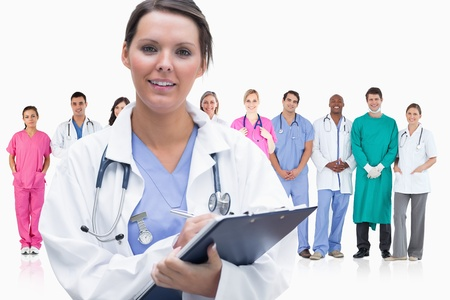 Woman doctor standing in front of her team in row holding clipboard on white background  photo