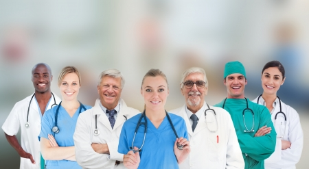 Smiling medical team standing in line on blurred background photo