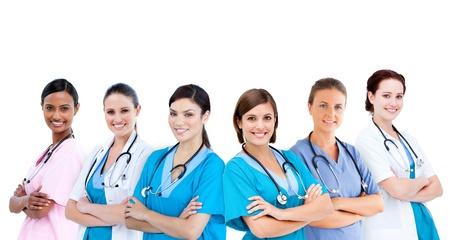 Smiling female hospital workers standing arms folded in line on white background photo