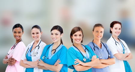Female hospital workers standing arms folded in line on blurred background photo