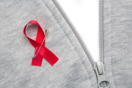 Aids awareness ribbon pinned on to grey zip jumper on white background photo