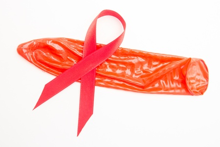 Red awareness ribbon lying on red condom on white background Stock Photo - 18132790