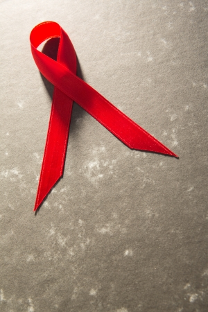 Awareness ribbon for aids on grey mottled background photo