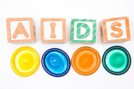 Wood blocks spelling out aids with four condoms on white background Stock Photo - 18133087