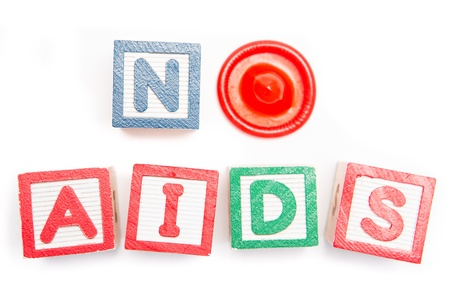 No aids spelled out in blocks and a condom on white background Stock Photo - 18133071