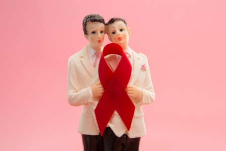 Gay groom cake toppers with red awareness ribbon on pink background photo