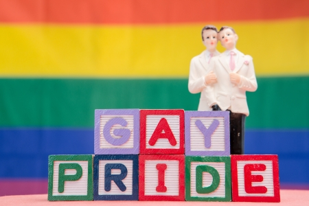 Blocks spelling gay pride with gay groom cake topper on rainbow background photo
