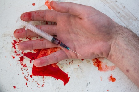 Lifeless hand holding bloody syringe in pool of blood photo