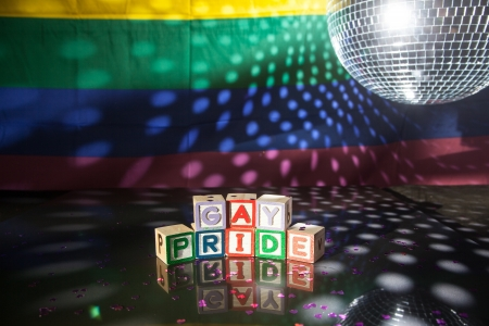 Block spelling gay pride under light of disco ball with rainbow flag photo