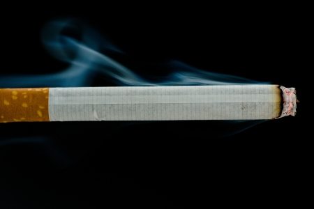 cigarette smoke: Lit cigarette on black background