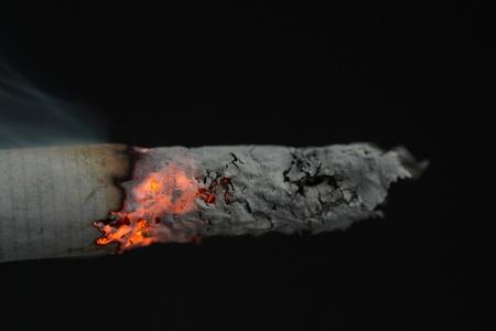 Close up of burning cigarette on black background Stock Photo