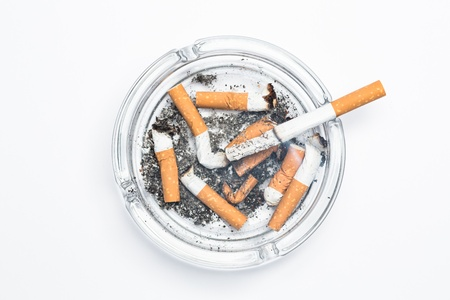 Overhead of burning cigarette in ashtray on white background photo