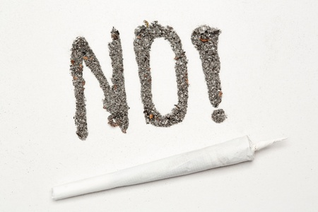 No with exclamation mark spelled out in ash with a joint on white background photo