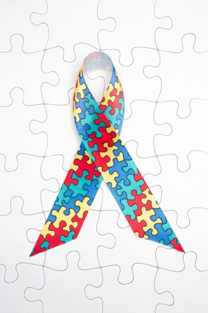 awareness: Awareness ribbon for autism and aspergers on white jigsaw background
