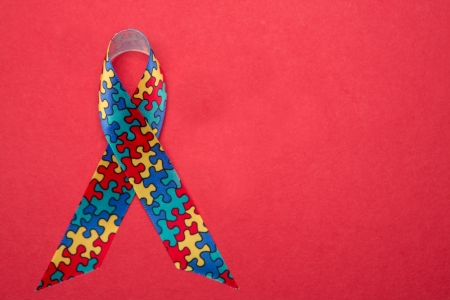 autism: Ribbon for autism and aspergers awareness with copy space on red background