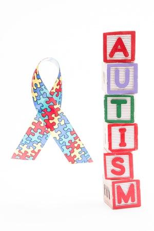 Autism awareness ribbon beside stacked blocks spelling autism on white background Stock Photo - 18129657