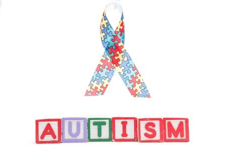Autism awareness ribbon above letter blocks spelling autism on white background Stock Photo - 18129556