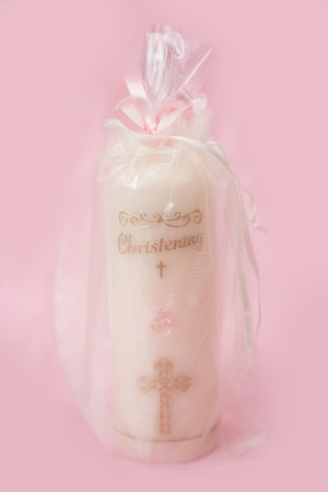 Christening candle for a girl on pink background photo