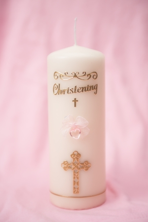 Christening candle with pink detail on textured pink background photo